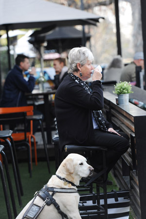 Woman sits at a bench in a cafe drinking a cup of coffee, with seeing eye dog sitting beside her.