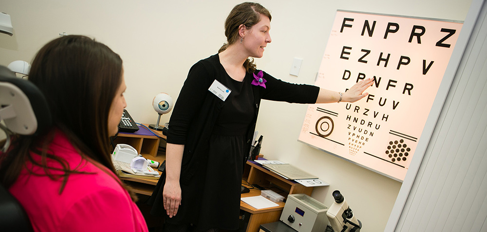 Eye specialist is pointing to a row on the eye chart in front of seated client.